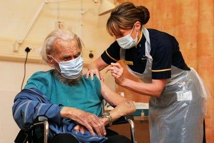 Trevor Cowlett, de 88 años, recibe la vacuna COVID-19 de la Universidad de Oxford / AstraZeneca en el Hospital Churchill en Oxford, Gran Bretaña, el 4 de enero de 2021. Steve Parsons / Pool vía REUTERS