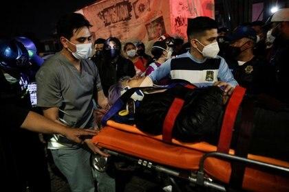 Los rescatistas transportan a una persona lesionada en una camilla desde un sitio donde un paso elevado de un metro colapsó parcialmente, mientras pasaba un tren, en la estación de Olivos, en la Ciudad de México, el 3 de mayo de 2021 (Reuters / Luis Cortes)