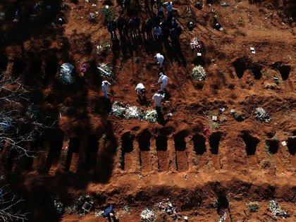 Vista aérea este martes desde un dron, de trabajadores enterrando a una de las víctimas mortales de la pandemia COVID-19 mientras familiares se despiden, en el cementerio de Vila Formosa, el más grande de América Latina, en Sao Paulo (Brasil). (EFE/ PAULO WHITAKER)