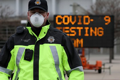 Un oficial guía el tráfico hacia un estacionamiento donde la Guardia Nacional Aérea de Colorado está examinando a las personas, que sospechan que están infectadas con la enfermedad del coronavirus (COVID-19), en una estación de pruebas de conducción, en Denver, Colorado, EE.UU. 14 de marzo de 2020. (REUTERS)