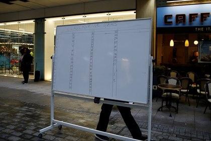 Un trabajador retira una pizarra con notas electorales de la sede del Partido Laborista después de las elecciones generales en Londres (REUTERS/Henry Nicholls)
