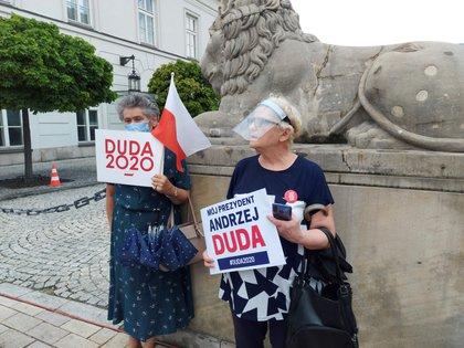 Dos mujeres asisten a un acto a favor del candidato conservador Andrzej Duda en el centro de Varsovia, este sábado, último día de campaña electoral en Polonia. EFE/ Clara  Palma