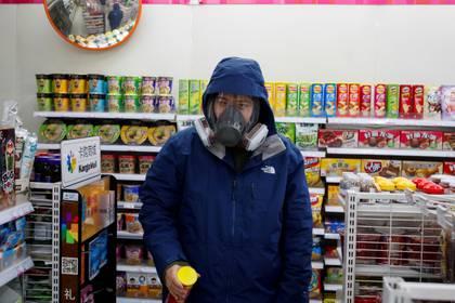 Escenas cotidianas: un hombre completamente cubierto hace sus compras en Beijing (REUTERS/Thomas Peter)