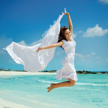 13173046 – beautiful girl with white scarf jumping on the beach
