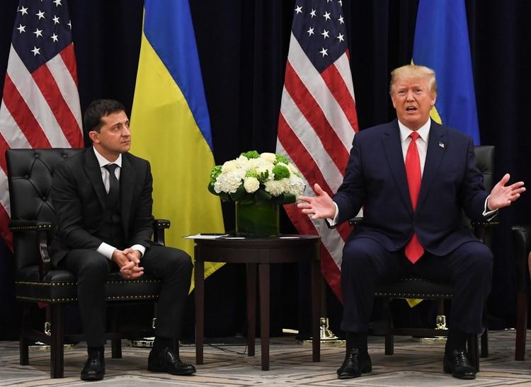 Donald Trump habla con el presidente ucraniano Volodymyr Zelensky (Photo by SAUL LOEB / AFP)