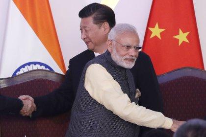En esta imagen de archivo, del 16 de octubre de 2016, el primer ministro de India, Narendra Modi, delante, y el presidente de China, Xi Jinping, al fondo, estrechan manos de otros mandatarios en la cumbre de los BRIC en Goa, India (AP Foto/ Manish Swarup, archivo)