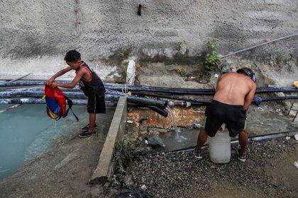 Marzo de 2019. Luego de varios días de apagones, un grupo de personas toma agua de una tubería de una construcción abandonada en la Avenida Baralt, en el centro de Caracas. (EFE/MIGUEL GUTIERREZ)