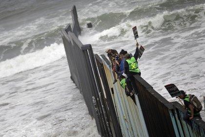 Pancartas pidiendo el acceso a territorio de los EEUU y la osadía de treparse a la barrera que entra en el Océano Pacífico, una de las imágenes simbólicas de lo que se vive en Tijuana (AP/Hans-Maximo Musielik)