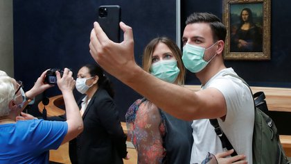 "Visitors, wearing protective face masks, make a selfie in front of the ""Mona Lisa"" (La Joconde) by Leonardo Da Vinci at the Louvre museum in Paris as the museum reopens its doors to the public after almost 4-month closure due to the coronavirus disease (COVID-19) outbreak in France, July 6, 2020. REUTERS/Charles Platiau"