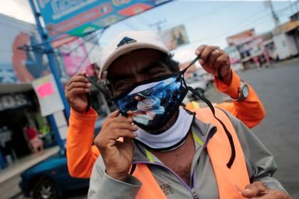 Un hombre ajusta una mascarilla protectora hecha a mano con la imagen de Jesucristo para su amigo en el mercado oriental de Managua, Nicaragua.  REUTERS/Oswaldo Rivas
