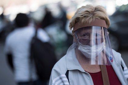Una mujer con tapabocas y protector entra el 14 de mayo de 2020 a la Vega Central, principal mercado de abastos de Santiago (Chile). EFE/Alberto Valdés/Archivo