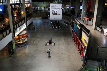 Un hombre mira su teléfono celular mientras camina por el hall del aeropuerto internacional de Guarulhos en medio del brote de coronavirus, cerca de Sao Paulo, Brasil, el 19 de mayo de 2020.REUTERS/Amanda Perobelli