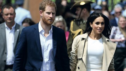 Britain's Prince Harry (C) and his wife Meghan (R) arrive at the Sydney Opera House in Sydney on October 16, 2018. - Prince Harry and Meghan have made their first appearances since announcing they are expecting a baby, kicking off a high-profile Pacific trip with a photo in front of Sydney's dazzling Opera House and posing with koalas. (Photo by DAN HIMBRECHTS / POOL / AFP)