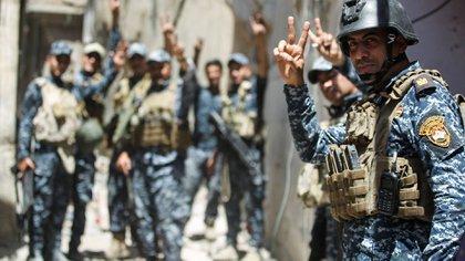 Tropas celebrando la victoria mientras avanzan por las calles de la ciudad vieja de Mosul(AFP)