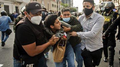 Agentes de seguridad se llevan detenido a un manifestante (ERNESTO BENAVIDES / AFP)