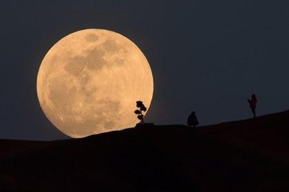 Una persona posa para una foto mientras la luna se levanta sobre Griffith Park en Los Angeles, California, el 30 de enero de 2018 (AFP)