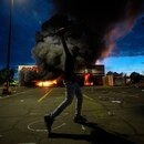 A man poses for a photo in the parking lot of an AutoZone store in flames, while protesters hold a rally for George Floyd in Minneapolis on Wednesday, May 27, 2020. Violent protests over the death of the black man in police custody broke out in Minneapolis for a second straight night Wednesday, with protesters in a standoff with officers outside a police precinct and looting of nearby stores. (Carlos Gonzalez/Star Tribune via AP)