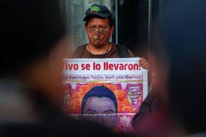 Un familiar de un estudiante desaparecido sostiene un cartel con su imagen mientras participa en una protesta frente a la Procuraduría General de la República (Foto: Reuters)