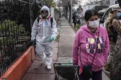Un trabajador municipal limpia y desinfecta las calles del barrio San Miguel de Santiago, el 7 de julio de 2020 en medio de la nueva pandemia de coronavirus (AFP)