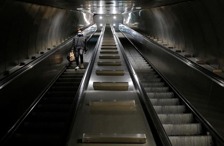 Un hombre con una máscara protectora se sube a una escalera mecánica en una estación de metro vacía, en el cuarto día de un bloqueo en toda Italia impuesto para frenar el brote de coronavirus, en Roma (Reuters)