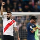 Lucas Pratto of Argentina's River Plate celebrates scoring his side's opening goal Pablo Perez of Argentina's Boca Juniors walks pass during the Copa Libertadores final soccer match at the Santiago Bernabeu stadium in Madrid, Spain, Sunday, Dec. 9, 2018. (AP Photo/Manu Fernandez)