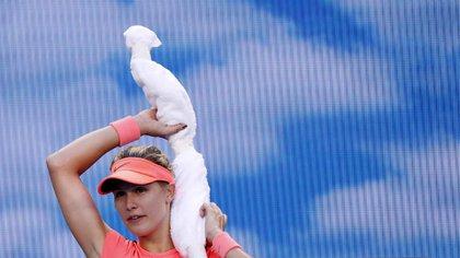 La canadiense Eugenie Bouchard cubre su nuca para buscar un refresco en la caliente ciudad de Melbourne, Australia, durante el partido que disputó contra Simona Halep (REUTERS)