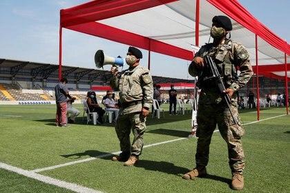 Foto de archivo. Los soldados montan guardia mientras los miembros del personal médico esperan recibir la primera inyección con una dosis de la vacuna contra la enfermedad del coronavirus Sinopharm (COVID-19) en el estadio Ollantaytambo en Lima, Perú, 19 de febrero de 2021. REUTERS / Sebastian Castaneda