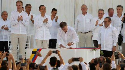 """La firma de del entonces presidente colombiano Juan Manuel Santos del acuerdo de Paz, el 24 de noviembre de 2016. A su derecha espera Rodrigo """"Timochenko"""" Londoño, de las FARC (AP)"""