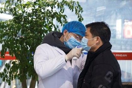Un médico le toma la temperatura a un hombre en el aeropuerto de Changsha, provincia de Hunan, China, (REUTERS/Thomas Peter)