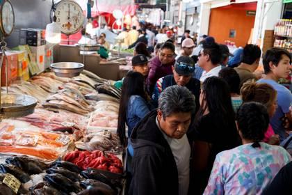 Luis Martín corta y limpia pescado velozmente en La Nueva Viga de Ciudad de México, el mercado más grande de América Latina, mientras atrae con avidez a los centenares de clientes que acuden en estos días de Cuaresma a hacer la compra, más pendientes de la tradición que de la pandemia de coronavirus. (Foto: EFE/ José Méndez)