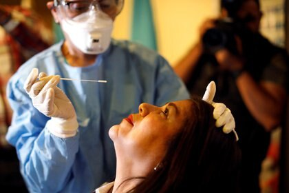 Una médica en Guatemala toma con un hisopo una muestra de saliva de una mujer que provino de Europa - REUTERS/Luis Echeverria