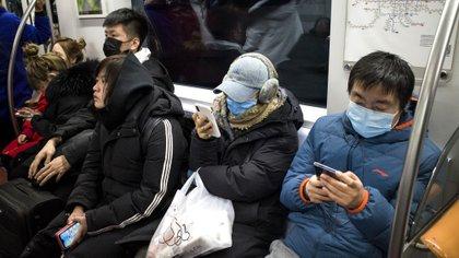 Pasajeros del tres subterráneo de Beijing (Foto de Noel Celis/ AFP)