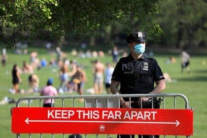 FOTO DE ARCHIVO: Un oficial del Departamento de Policía de la Ciudad de Nueva York (NYPD) con una mascarilla se encuentra en la entrada del Sheep Meadow en Central Park durante el brote de coronavirus (COVID-19), en Manhattan, Nueva York, EEUU. 15 de mayo de 2020. REUTERS/Andrew Kelly/File Photo