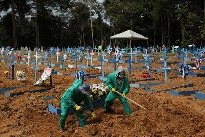 Sepultureros con trajes de protección enterrando a víctimas del coronavirus en un cementerio de Manaos, Brasil, el 26 de junio de 2020 (REUTERS/Bruno Kelly)