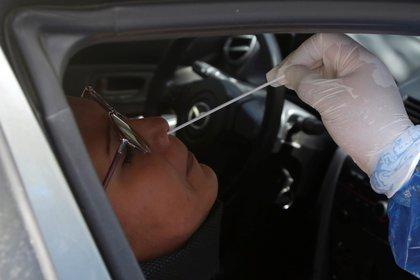 Profesional de la salud realizando prueba PCR para COVID-19 a una señora en un barrio de Cartagena / (EFE/Ricardo Maldonado Rozo).