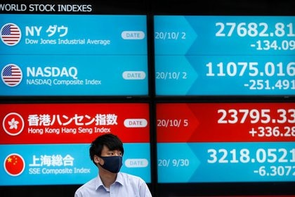 FILE PHOTO: A passersby wearing a protective face mask stands in front of a screen displaying world stock indexes outside a brokerage, in Tokyo, Japan October 5, 2020. REUTERS/Issei Kato