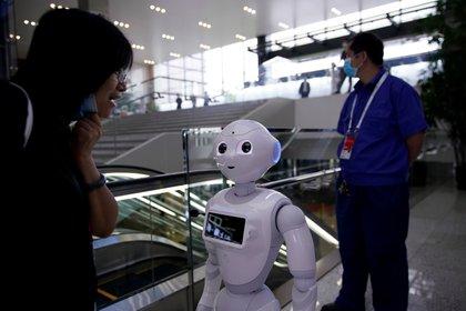 Las personas que usan mascarillas después del brote de la enfermedad del coronavirus (COVID-19) se ven cerca de un robot en la sede de la Conferencia Mundial de Inteligencia Artificial (WAIC) en Shanghai, China, el 9 de julio de 2020. REUTERS / Aly Song