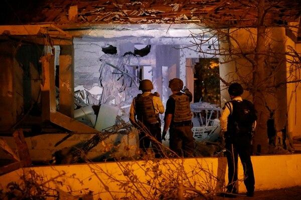 Personal de seguridad israelí controla los daños de una casa golpeada por un cohete palestino en Ashkelon (REUTERS/ Amir Cohen)