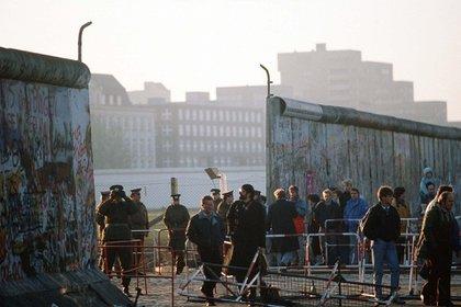 Policía del Este vigilando a la gente mientras cruza el muro el 14 de noviembre de 1989 (F A Archive/Shutterstock)