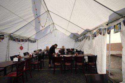 Una empleada de un restaurante limpia las mesas de un restaurante mexicano en La Mirada, California, el martes 24 de noviembre de 2020. (AP Foto/Jae C. Hong)
