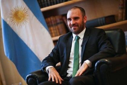 El ministro de Economía argentino, Martín Guzmán, posa junto a una bandera nacional