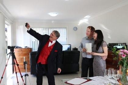 Lou Szymkow se toma una selfie con la pareja Peter Andrews y Hoang Nguyen después de oficiar una boda privada a el domicilio,  en Sydney, Australia (imagen tomada el 19 de mayo de 2020.  REUTERS/Loren Elliott)