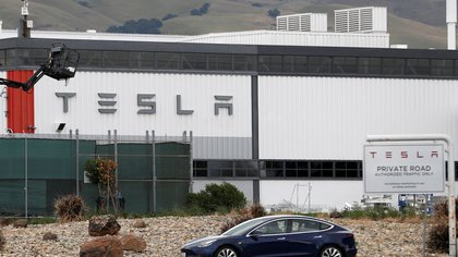 FILE PHOTO: A Tesla vehicle drives past Tesla's primary vehicle factory after CEO Elon Musk announced he was defying local officials' coronavirus disease (COVID-19) restrictions by reopening the plant in Fremont, California, U.S. May 11, 2020. REUTERS/Stephen Lam/File Photo