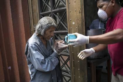 Un hombre utiliza bolsas de plástico como guantes desechables improvisados para tomar una taza de sopa gratis, en Lima, Perú (AP Foto/Rodrigo Abd)