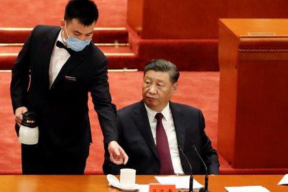 El jefe de estado chino, Xi Jinping, es atendido por un asistente durante una cumbre en el Gran Hall del Pueblo de China, en Beijing (Reuters)