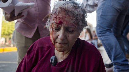 NI001. MANAGUA (NICARAGUA), 18/04/2018.- La activista de la Red de Mujeres contra la Violencia Ana Quiroz sangra en el suelo tras ser golpeada por las fuerzas de choque del gobierno de Ortega