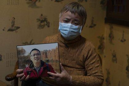 Zhong Hanneng sostiene un retrato de su padre, Peng Yi, quien no fue hospitalziado por no tener un test positivo (AP)