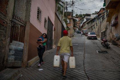 Un hombre carga dos recipientes plásticos de 25 litros de agua cada uno (EFE/ Miguel Gutiérrez)