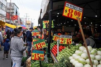 FOTO DE ARCHIVO: La gente mira carteles con precios de productos fuera de un mercado conocido como La Merced en la Ciudad de México, 25 de  junio de 2020. REUTERS/Henry Romero