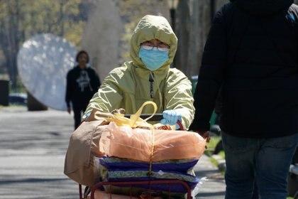 Una mujer con una máscara y una capucha camina con su carrito de compras durante el brote de coronavirus en Harlem, Manhattan (Reuters)